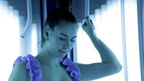 Красивая девушка со здоровым положением тела в солярии спа имеет красивую диаграмму Tan, кожа видеоматериал