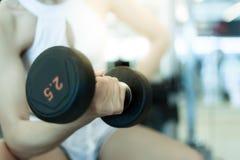 Красивая девушка спорта поднимает гантель для приобретать ее бицепс стоковая фотография rf