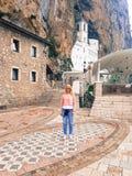 Красивая девушка стоит на входе к старому правоверному монастырю стоковое изображение rf