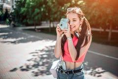 Красивая девушка стоящее снаружи на дороге и изображение принимать Она смотрит через lenz и усмехаться Девушка имеет музыку стоковое фото rf