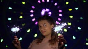 Красивая девушка счастлива с праздником с фейерверками в ее руках движение медленное HD акции видеоматериалы