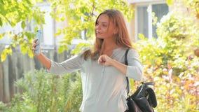 Красивая девушка с длинными волосами делает selfie на его съемке smartphone outdoors стабилизированной видеоматериал