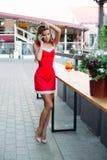 Красивая девушка с длинными ногами в красном платье говоря на телефоне Стоковое Изображение RF