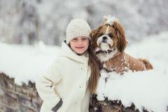 Красивая девушка с ее собакой на снеге в зиме стоковые фотографии rf