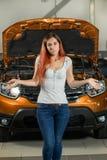 Красивая девушка с запутанностью стоит около автомобиля с открытым h стоковая фотография