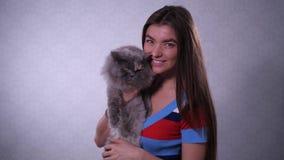 Красивая девушка с котом ревя на камере в ее руках 4K медленный Mo сток-видео