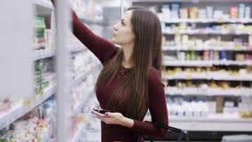 Красивая девушка с красной корзиной выбирая йогурт в разделе бакалеи на супермаркете акции видеоматериалы