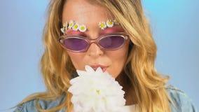 Красивая девушка с маргаритками вместо бровей наслаждаясь сладким нюхом георгинов сток-видео