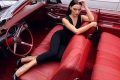 Красивая девушка с темными волосами в элегантных одеждах представляя в luxur Стоковые Фото