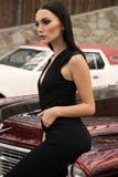 Красивая девушка с темными волосами в элегантных одеждах представляя в luxur Стоковое Изображение