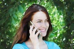 Красивая девушка с темными волосами говоря на телефоне и смеясь над на фоне зеленых деревьев Стоковые Фото
