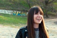 Красивая девушка с челкой и длинными волосами смеется над в жилете и кожаной куртке Стоковые Фотографии RF