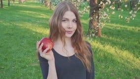 Красивая девушка с яблоком в ее руках против фона яблоневого сада Женщина хочет съесть яблоко видеоматериал