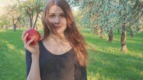 Красивая девушка с яблоком в ее руках против фона яблоневого сада Женщина хочет съесть яблоко акции видеоматериалы