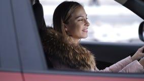 Красивая девушка управляет автомобилем, стопами, улыбками и приводами с 4K медленного Mo акции видеоматериалы