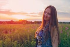 Красивая девушка усмехаясь в поле захода солнца стоковое изображение rf