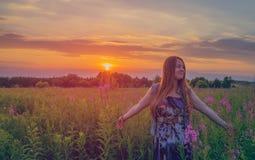 Красивая девушка усмехаясь в поле захода солнца стоковые фото