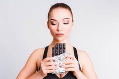 Красивая девушка фитнеса на светлом - серая предпосылка с шоколадом Концепция общаться с желанием съесть старье стоковая фотография rf