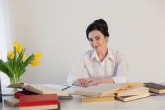 Красивая девушка читает книги на таблице подготавливая для экзамена Стоковое Фото