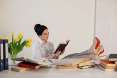 Красивая девушка читает книги на таблице подготавливая для экзамена Стоковое фото RF