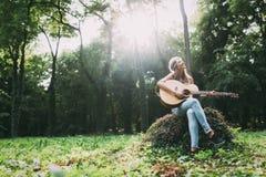 Красивая девушка hippie играя гитару Стоковая Фотография