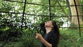 красивая девушка 4k в черном handmade платье стоя внутри овальной конструкции беседки металла сада лета касаясь ей акции видеоматериалы