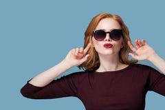 Красивая девушка redhead в поцелуе губной помады черных солнечных очков красном на голубой предпосылке стоковая фотография rf