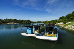 Красивая деревня в Terengganu, Малайзии с предпосылкой традиционной причаленной шлюпки рыболова Стоковое Фото