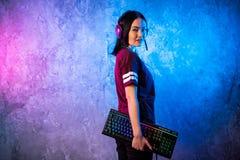 Красивая дружелюбная Pro девушка представляя с клавиатурой в ее руках, нося стекла ленты Gamer Привлекательная девушка идиота стоковая фотография