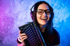 Красивая дружелюбная Pro девушка представляя с клавиатурой в ее руках, нося стекла ленты Gamer Привлекательная девушка идиота стоковые изображения rf