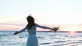 Красивая европейская невеста с первоначально букетом handmade закручивать на море на заходе солнца и танцевать на пляже сток-видео