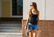 Красивая девушка битника с солнечными очками доски конька нося Стоковые Изображения
