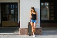 Красивая девушка битника с солнечными очками доски конька нося Стоковое Фото