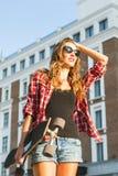 Красивая девушка битника с солнечными очками доски конька нося Стоковая Фотография