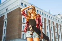 Красивая девушка битника с солнечными очками доски конька нося Стоковое Изображение RF