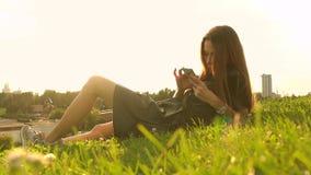 Красивая девушка брюнет в черном платье используя ее smartphone на лужайке мечтает лето видео 4K акции видеоматериалы
