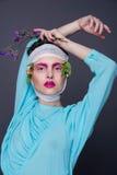 Красивая девушка брюнет девушки в голубом платье моды с ярким романтичным составом, цветках на ее голове и ветви Стоковая Фотография