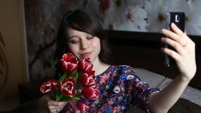 Красивая девушка брюнет делая selfie с красным цветом цветет тюльпаны на черном smatfon сток-видео