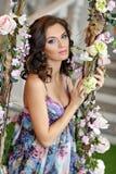 Красивая девушка брюнет ждать младенца в фиолетовом платье сидит Стоковое Фото