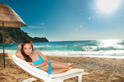 Красивая девушка брюнет загорая на sunbed на море Стоковые Изображения