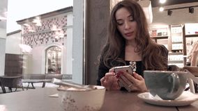 Красивая девушка брюнет используя ее мобильный телефон в кафе видео 4K видеоматериал