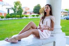 Красивая девушка брюнет отдыхая на открытом воздухе сидеть, мечтая о человеке, бизнес-леди с длинными волосами Способ Стоковые Фото