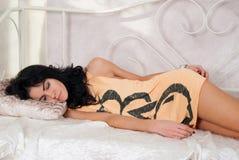 Красивая девушка брюнет спать на кровати стоковое фото rf