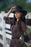 Красивая девушка брюнет с взглядом страны, outdoors сняла около деревянной загородки, деревенского стиля привлекательная женщина  Стоковые Фотографии RF