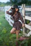 Красивая девушка брюнет с взглядом страны, outdoors сняла около деревянной загородки, деревенского стиля привлекательная женщина  Стоковое Изображение RF