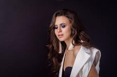 Красивая девушка брюнет с пропуская волосами на темной предпосылке в белой куртке Стоковое Изображение RF