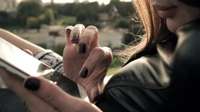 Красивая девушка брюнет с темным маникюром используя ее smartphone в парке мечтает лето 4K закрывают вверх по видео сток-видео