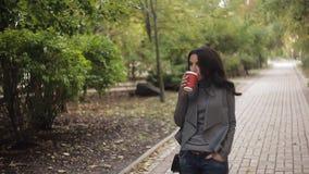 Красивая девушка выпивает кофе в парке Свет осени мягкий сток-видео