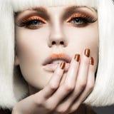 Красивая девушка в белом парике, с составом золота и ногтями Праздничное изображение Сторона красотки Стоковое фото RF