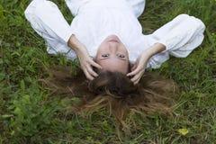 Красивая девушка в белом платье лежа вниз на траве Стоковое фото RF